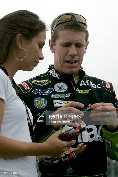Carl Edwards driver of the Aflac Ford talks with his wife Katherine Downey on the grid prior to the NASCAR Sprint Cup Series Heluva Good Sour Cream...