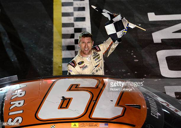 Carl Edwards driver of the ARRIS Toyota celebrates with the checkered flag after winning the NASCAR Sprint Cup Series Bojangles' Southern 500 at...