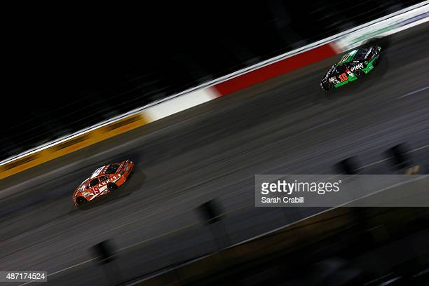 Carl Edwards driver of the ARRIS Toyota leads Danica Patrick driver of the GoDaddy Chevrolet during the NASCAR Sprint Cup Series Bojangles' Southern...