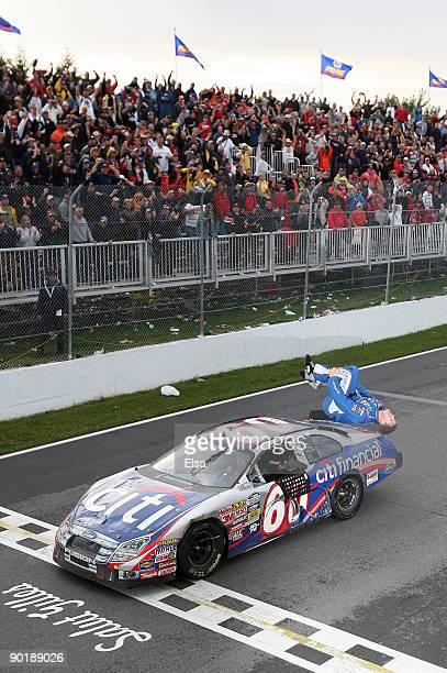 Carl Edwards driver of the CitiFinancial Ford celebrates his win with his signature backflip after the Napa Auto Parts 200 on August 30 2009 at the...