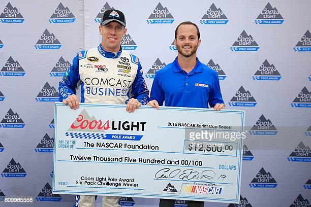Carl Edwards driver of the Comcast Business Toyota poses with the Coors Light Pole Award and his donation to Speedway Children's Charities after...