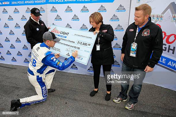 Carl Edwards driver of the Comcast Business Toyota signs his donation to Speedway Children's Charities after winning the Coors Light Pole Award...
