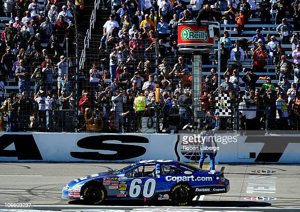 Carl Edwards driver of the Copartcom Ford catches the checkered flag after winning the NASCAR Nationwide Series O'Reilly Auto Parts Challenge at...