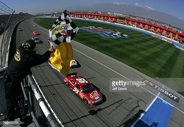 Carl Edwards, driver of the Dish Network Ford, crosses the finish line under caution to win the NASCAR Sprint Cup Series Auto Club 500 at the Auto...