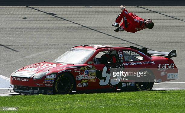 Carl Edwards, driver of the Dish Network Ford, performs a back flip after winning the NASCAR Sprint Cup Series Auto Club 500 at the Auto Club...