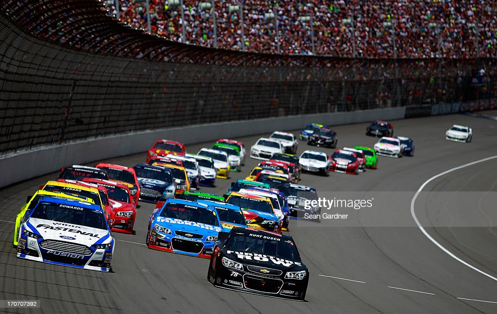 Carl Edwards, driver of the #99 Fastenal Ford, and Kurt Busch, driver of the #78 Furniture Row/Sealy Chevrolet, lead the field into turn one during the NASCAR Sprint Cup Series Quicken Loans 400 at Michigan International Speedway on June 16, 2013 in Brooklyn, Michigan.