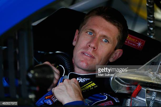 Carl Edwards, driver of the Fastenal Ford, sits in his car in the garage area during practice for the NASCAR Sprint Cup Series Camping World RV Sales...