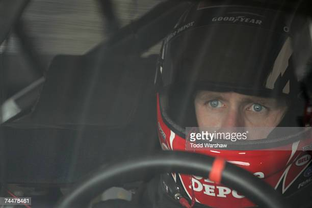 Carl Edwards driver of the Office Depot Ford sits in his car in the garage during practice for the NASCAR Nextel Cup Series Pocono 500 at Pocono...
