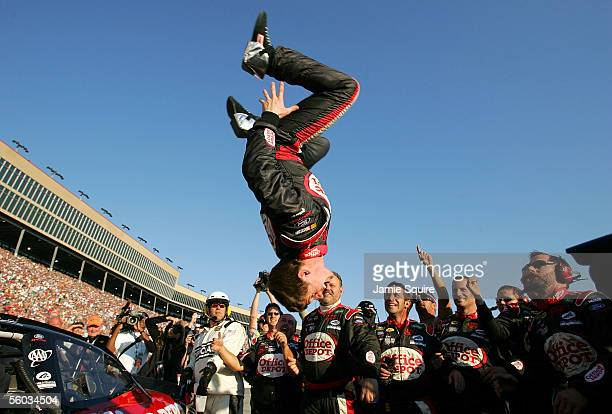 Carl Edwards driver of the Roush Racing Ford performs a backflip as crew members look on after winning the NASCAR Nextel Cup Series Bass Pro Shops...