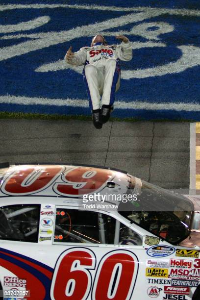 Carl Edwards, driver of the Save-A-Lot Ford, performs a backflip after winning the NASCAR Nationwide Series Ford 300 at Homestead-Miami Speedway on...
