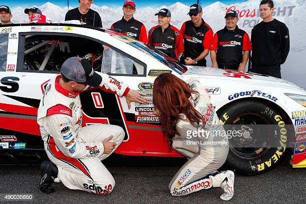 Carl Edwards driver of the Sport Clips Toyota and Miss Coors Light Amanda Mertz affix the Coors Light Pole Award decal after Edwards qualified on the...