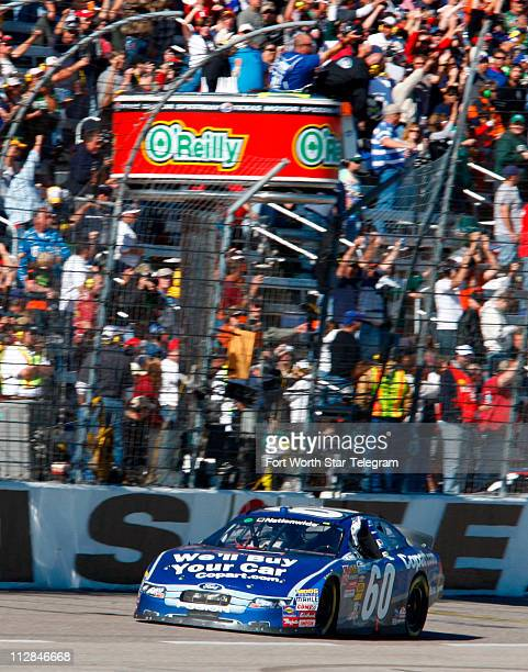 Carl Edwards passes under the green/white checkered flag at the finish of the NASCAR Nationwide Series O'Reilly Challenge 300 at Texas Motor Speedway...