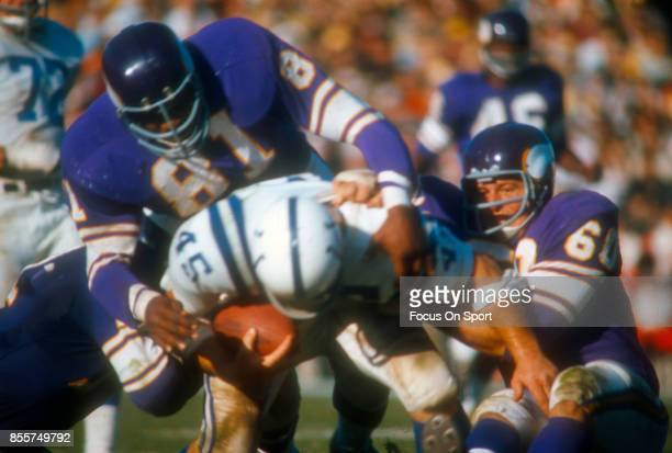 Carl Eller and Roy Winston of the Minnesota Vikings tackles Jerry Hill of the Baltimore Colts during an NFL football game circa 1967 at Metropolitan...