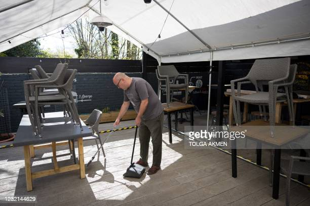 Carl Elliott, manager of The Village Pub, cleans and prepares the outdoor seating area his pub in Walthamstow, northeast London on April 6 ahead of...