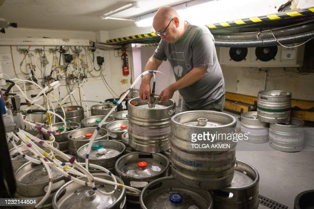 Carl Elliott, manager of The Village Pub, connects new beer barrels to the taps at his pub in Walthamstow, northeast London on April 6 ahead of...