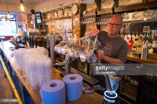 Carl Elliott, manager of The Village Pub, removes cling film used to cover the beer taps during the third Covid-19 lockdown, at his pub in...