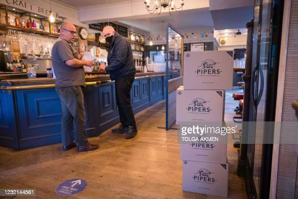 Carl Elliott , manager of The Village Pub, takes delivery of boxes of crisps at his pub in Walthamstow, northeast London on April 6 as he prepares...
