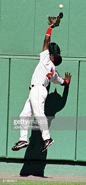 Carl Everett centerfielder for the Boston Red Sox tries unsuccessfully to snag the ball on a deep hit by Derek Jeter of the New York Yankees in the...
