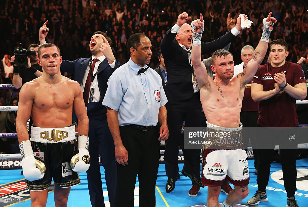 Carl Frampton (2R) celebrates a points victory over Scott Quigg (L) as his manager Barry McGuigan (4L) reacts after their World Super-Bantamweight title contest at Manchester Arena on February 27, 2016 in Manchester, England. Frampton's victory united the WBA and IBF titles.
