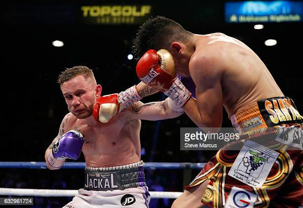 Carl Frampton gets hit with a punch from Leo Santa Cruz during the 12th round of their WBA featherweight title fight at MGM Grand Garden Arena on...