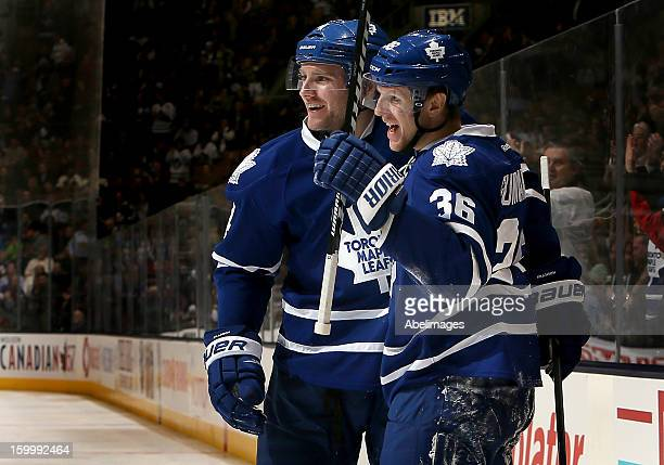 Carl Gunnarsson and Cody Franson of the Toronto Maple Leafs celebrate a Carl Gunnarsson goal against the New York Islanders during NHL action at the...