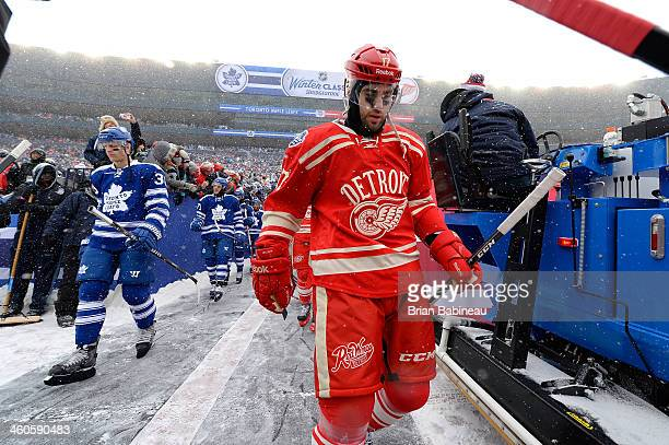 Carl Gunnarsson and David Clarkson of the Toronto Maple Leafs and Patrick Eaves of the Detroit Red Wings make their way to the ice surface for the...
