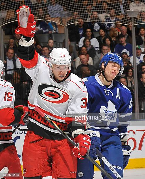 Carl Gunnarsson of the Carolina Hurricanes celebrates a first period goal as Mikhail Grabovski of the Toronto Maple Leafs looks on during NHL game...