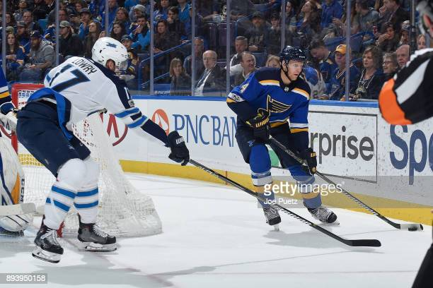 Carl Gunnarsson of the St Louis Blues handles the puck as Adam Lowry of the Winnipeg Jets pressures at Scottrade Center on December 16 2017 in St...