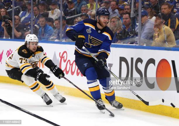 Carl Gunnarsson of the St Louis Blues is chased by Charlie McAvoy of the Boston Bruins during the third period of Game Three of the 2019 NHL Stanley...