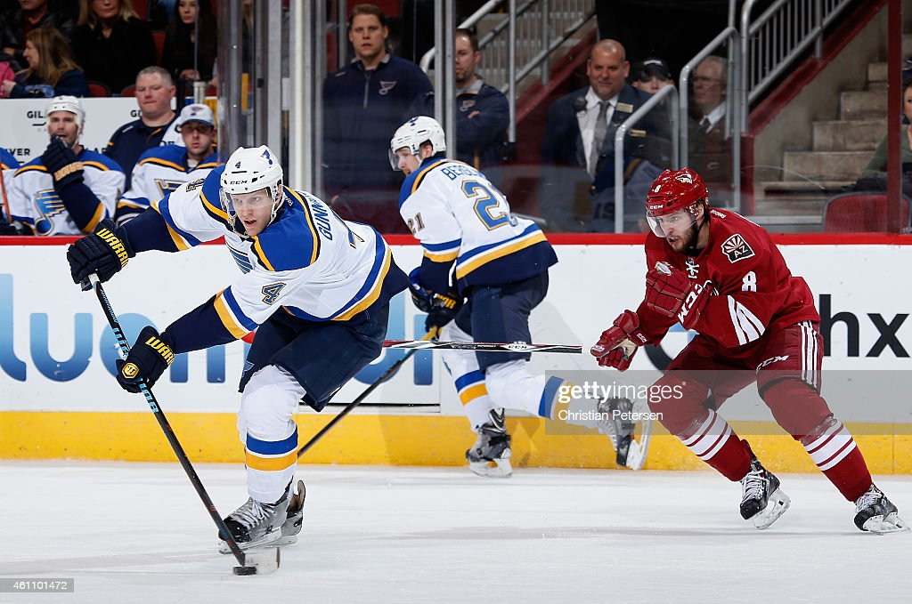 Carl Gunnarsson #4 of the St. Louis Blues passes the puck ahead of Tobias Rieder #8 of the Arizona Coyotes during the first period of the NHL game at Gila River Arena on January 6, 2015 in Glendale, Arizona.