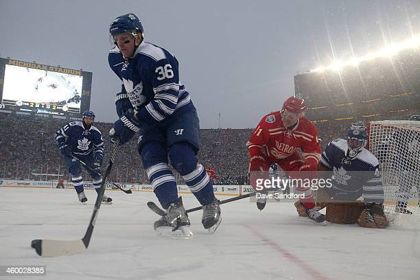 Carl Gunnarsson of the Toronto Maple Leafs controls the puck in the defensive zone while under pressure from Daniel Alfredsson of the Detroit Red...