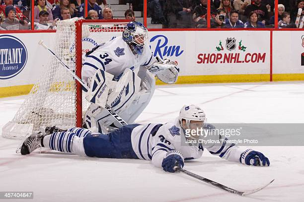 Carl Gunnarsson of the Toronto Maple Leafs drops to the ice to block a pass as team mate guards his net during an NHL game against the Ottawa...