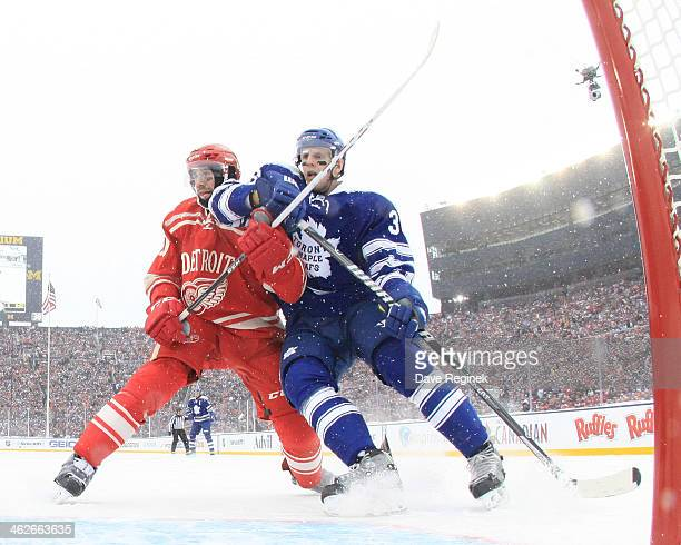 Carl Gunnarsson of the Toronto Maple Leafs is tied up going to the net by Drew Miller of the Detroit Red Wings during the Bridgestone NHL Winter...