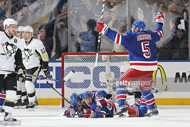 Carl Hagelin, Dominic Moore and Dan Girardi of the New York Rangers celebrate after a game winning goal in overtime to defeat the Pittsburgh Penguins...