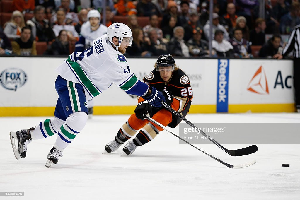 Carl Hagelin #26 of the Anaheim Ducks and Yannick Weber #6 of the Vancouver Canucks lunge for a loose puck during the third period of a game at Honda Center on November 30, 2015 in Anaheim, California.