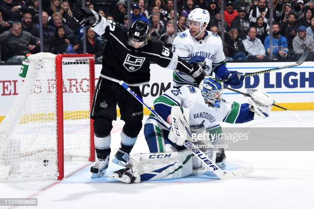 Carl Hagelin of the Los Angeles Kings skates in the crease as goaltender Jacob Markstrom of the Vancouver Canucks takes his stick and Derrick Pouliot...