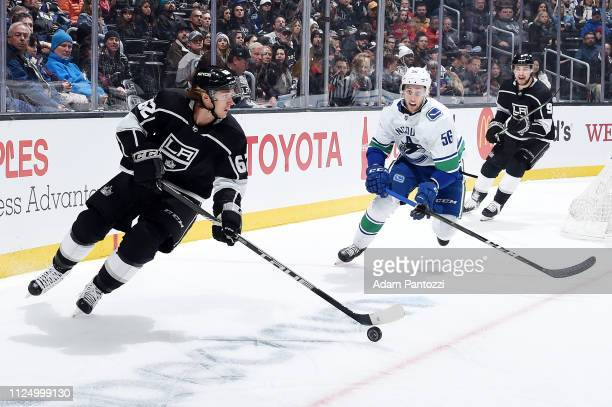 Carl Hagelin of the Los Angeles Kings skates with the puck while pursued by Guillaume Brisebois of the Vancouver Canucks during the first period of...