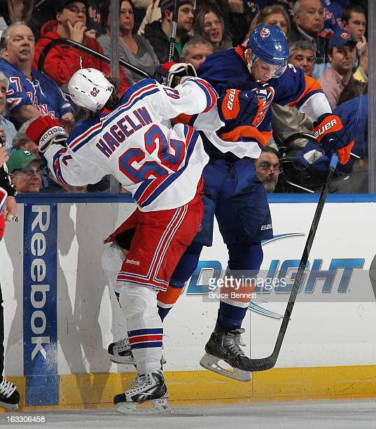 Carl Hagelin of the New York Rangers hits Travis Hamonic of the New York Islanders during the second period at the Nassau Veterans Memorial Coliseum...