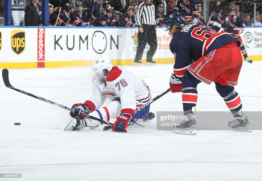 Carl Hagelin #62 of the New York Rangers knocks down P.K. Subban #76 of the Montreal Canadiens as they battle for the puck at Madison Square Garden on November 23, 2014 in New York City.
