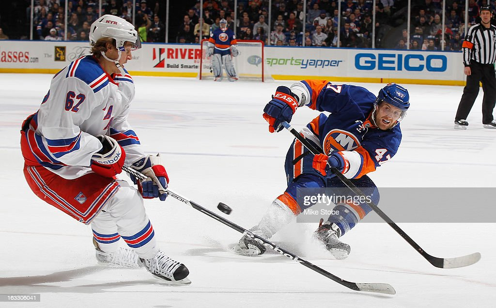 Carl Hagelin #62 of the New York Rangers pursues the puck against Andrew MacDonald #47 of the New York Islanders at Nassau Veterans Memorial Coliseum on March 7, 2013 in Uniondale, New York.