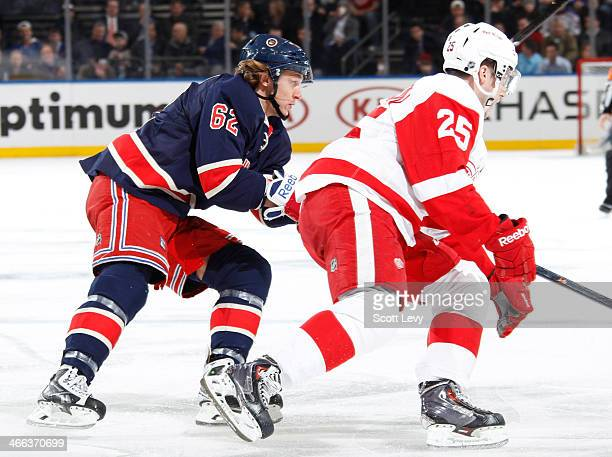 Carl Hagelin of the New York Rangers skates against Cory Emmerton of the Detroit Red Wings at Madison Square Garden on January 16 2014 in New York...
