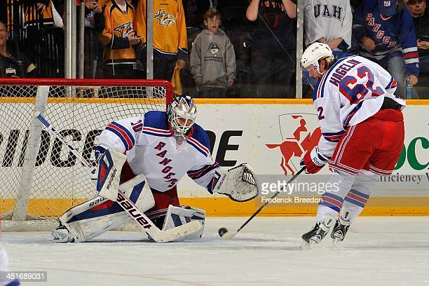 Carl Hagelin of the New York Rangers takes a shot on goalie Henrik Lundqvist during warms up prior to a game against of the Nashville Predators at...
