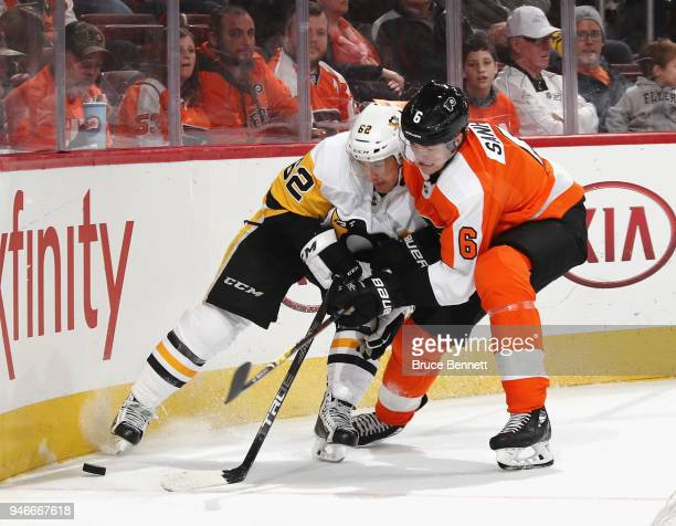 Carl Hagelin of the Pittsburgh Penguins and Travis Sanheim of the Philadelphia Flyers pursue the puck along the boards during the third period in...