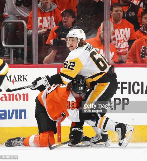 Carl Hagelin of the Pittsburgh Penguins checks Nolan Patrick of the Philadelphia Flyers during the first period in Game Three of the Eastern...