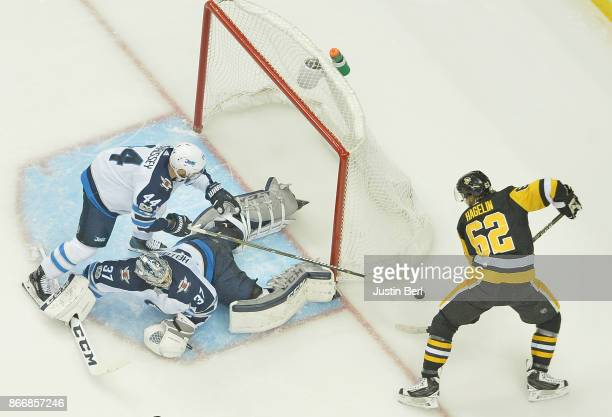 Carl Hagelin of the Pittsburgh Penguins has the puck poked off his stick by Josh Morrissey of the Winnipeg Jets in the second period during the game...