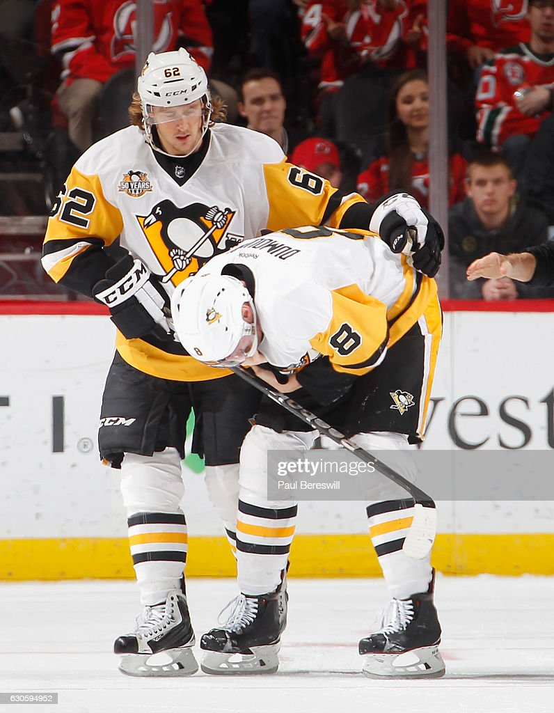 Carl Hagelin #62 of the Pittsburgh Penguins helps teammate Brian Dumoulin #8 off the ice after Dumoulin was injured in the second period of an NHL hockey game at Prudential Center on December 27, 2016 in Newark, New Jersey. Penguins won 5-2.