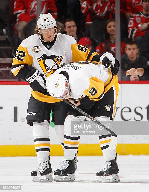Carl Hagelin of the Pittsburgh Penguins helps teammate Brian Dumoulin off the ice after Dumoulin was injured in the second period of an NHL hockey...