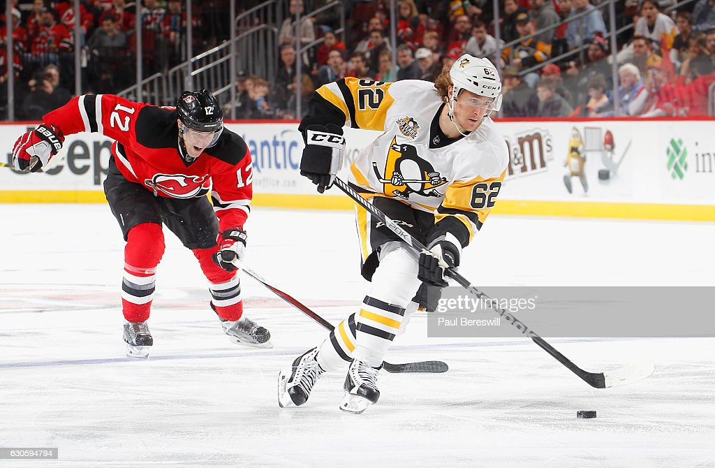 Carl Hagelin #62 of the Pittsburgh Penguins leads the breakaway from Ben Lovejoy #12 of the New Jersey Devils in which he scored a goal in the third period of an NHL hockey game at Prudential Center on December 27, 2016 in Newark, New Jersey. Penguins won 5-2.
