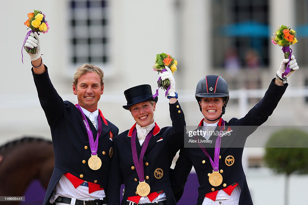Carl Hester, Laura Bechtolsheimer and Charlotte Dujardin of Great Britain celebrate with their gold medals during the medal cerermony for the Team Dressage on Day 11 of the London 2012 Olympic Games at Greenwich Park on August 7, 2012 in London, England.
