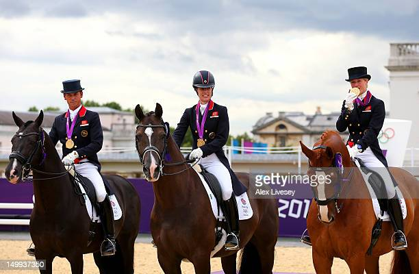Carl Hester on Uthopia Charlotte Dujardin of Great Britain on Valegro and Laura Bechtolsheimer on Mistral Hojris celebrate with their gold medals...